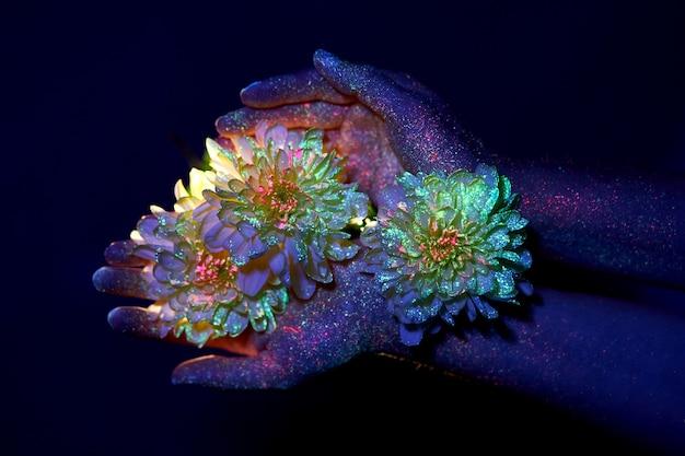 手のひらに花を持つ紫外線の女性の美しさの手。ハンドスキンケア用化粧品