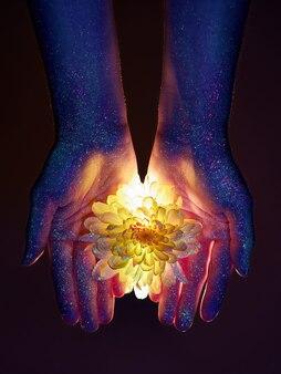 Красота рук женщины в ультрафиолетовом свете с цветами в ладонях. косметика для ухода за кожей рук