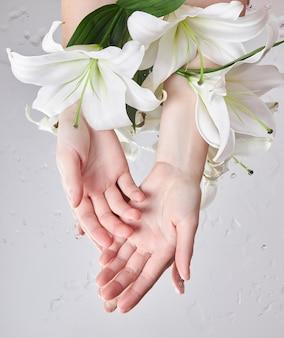 백합 꽃과 아름다움 손은 젖은 꽃 거울 보습에 테이블, 여자 아름다움 손에 거짓말. 손 피부 관리를위한 천연 꽃 화장품. 매끄러운 미인 피부, 주름 개선, 노화 방지