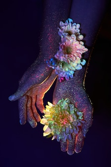 Beauty hands of a woman in ultraviolet light with flowers in the palms. cosmetics for hand skin care