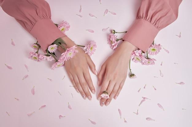 ピンクの花を持つ美の手の女性がテーブルの上にあります。ハンドスキンケア用の天然化粧品。完璧なネイル