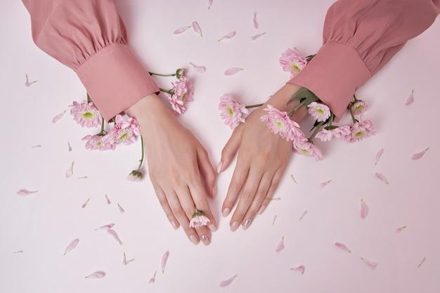 분홍색 꽃을 가진 미녀가 탁자 위에 있다. 손 피부 관리를 위한 천연 화장품. 완벽한 손톱