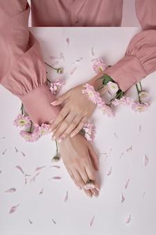 분홍색 꽃을 든 미녀가 탁자 위에 있다. 손 피부 관리를 위한 천연 화장품. 완벽한 손톱