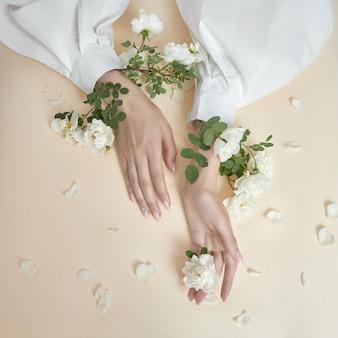 バラの花を持つ美の手の女性がテーブルの上にあります。ハンドスキンケア用の天然化粧品。ファッションメイク