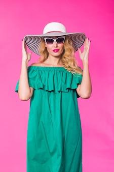 サングラスをかけている美しさの幸せなファッションモデルの女性。ポジティブな感情を表現し、笑顔。