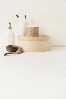 등나무 관, 분말, 칫솔, 흰색 테이블에 액체 비누에 귀 스틱과 미용 건강 관리 구성