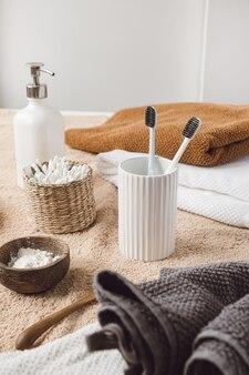 籐の棺、タオル、液体石鹸、ベージュのタオルに歯ブラシのイヤスティックを備えた美容ヘルスケア組成物