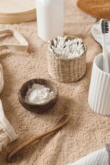 베이지 색 수건에 등나무 관, 수건, 분말, 칫솔에 귀 스틱이있는 미용 건강 관리 조성물