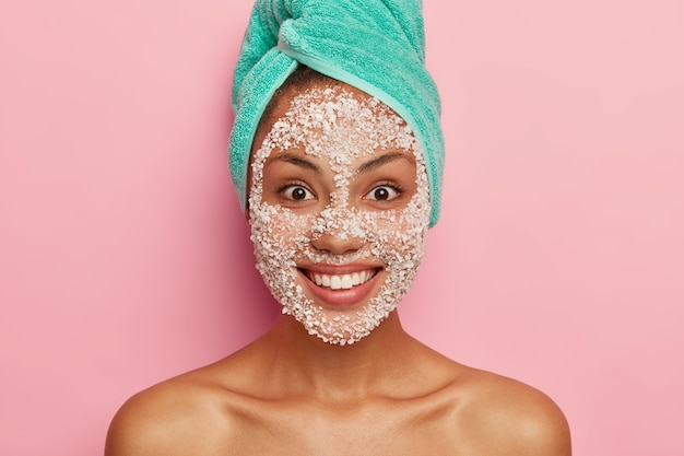 Beauty and health care concept. close up image of satisfied dark skinned female applies white scrub facial mask, cares about purity and softness of her complexion, has turquoise towel on head