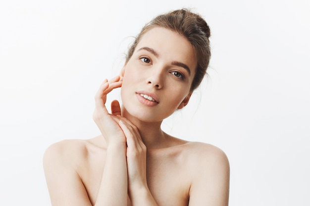 Beauty and health. young good-looking skinny caucasian girl with dark hair in bun hairstyle being naked with relaxed and happy expression, touching hand with hands.