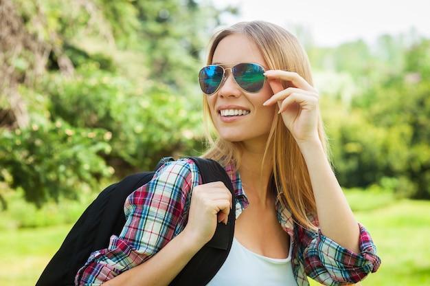 美容ハイキング。自然の中で立っている間彼女のバックパックを運び、サングラスを調整する美しい若い女性