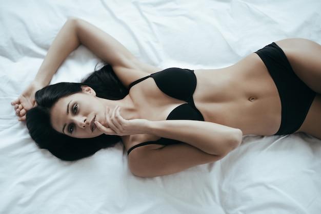 ベッドの美しさ。彼女の唇に指を保持しているランジェリーの魅力的な若い女性の上面図