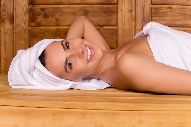 Красота в сауне. красивая молодая женщина, завернутая в полотенце, расслабляется в сауне и улыбается вам