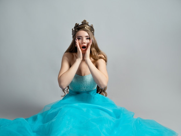 Красавица в шоке молодая красивая блондинка в пышном голубом платье