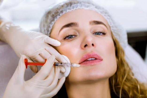 Салон инъекций. крупный план рук доктора с шприцем около женского лица. портрет красивой женщины с мягкой кожей