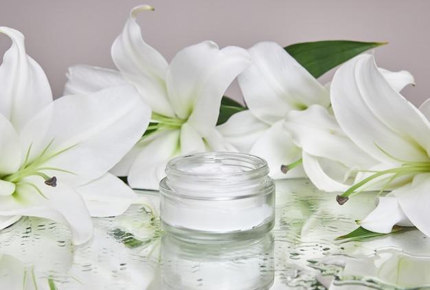Косметический крем beauty jar с цветами лилии лежит на столе, кремовый продукт в банке на влажном цветочном зеркале увлажняет. натуральная крем-косметика в цветочной баночке для ухода за кожей рук. гладкая красивая кожа