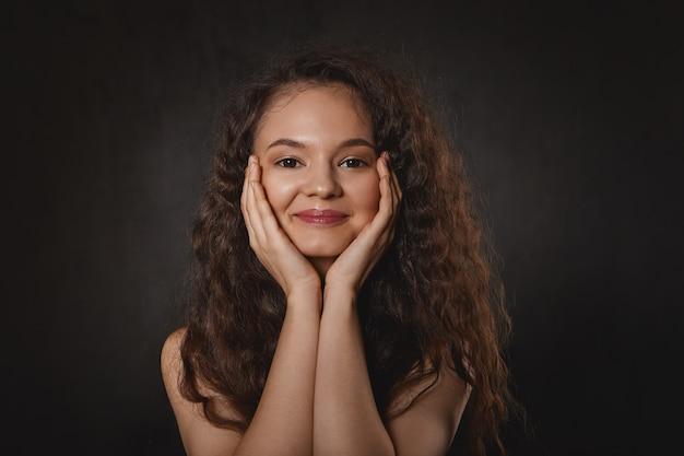 Концепция красоты, радости и счастья. портрет очаровательной очаровательной молодой женщины, положив подбородок на руки