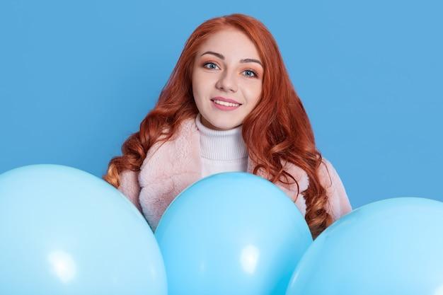 青い壁に隔離された楽しみを持って、幸せな表情を持つ女性、ポジティブなイベントを祝う女の子、ヘリウム風船を持つ美しさの楽しい女性の女の子。