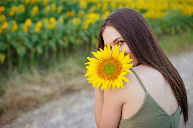 ひまわり自然を楽しんで、夕暮れ時のヒマワリのフィールドで笑いながらうれしそうな美少女。
