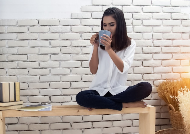 The beauty lady sitting on wooden chair, drinking coffee, relax time