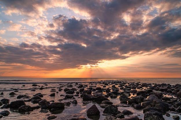 太陽が海に昇るときの暗い雲のある美しさの風景