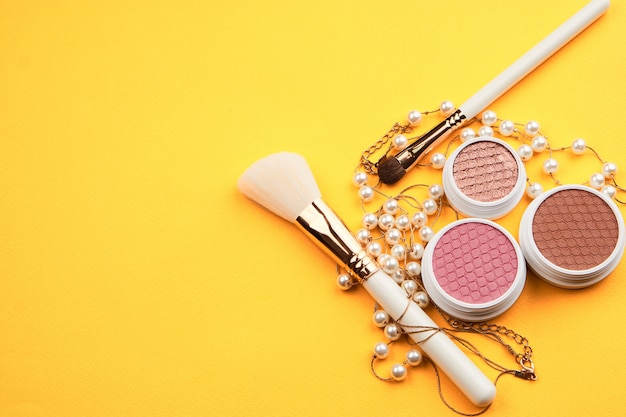 Beauty layout on a colored background with cosmetics and jewelry
