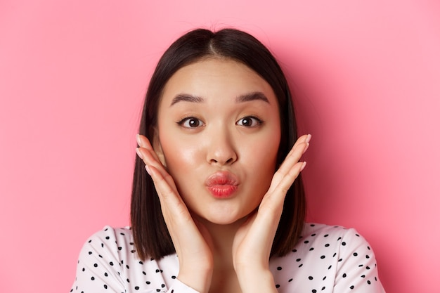 Beauty and lifestyle concept. close-up of adorable asian woman touching face, pucker lips in kiss, standing over pink.