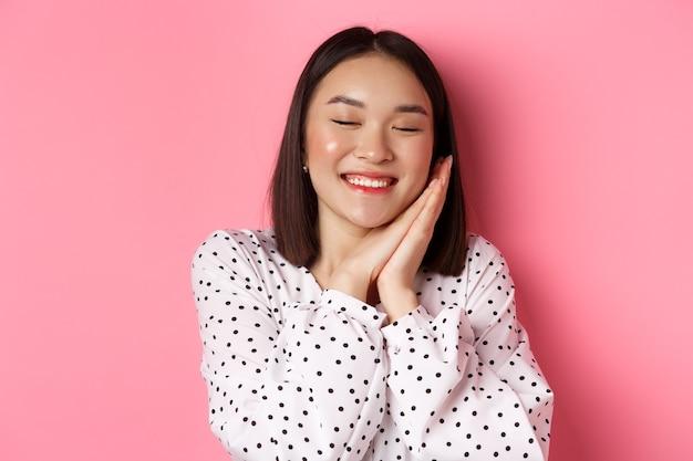 Concetto di bellezza e stile di vita. primo piano di una bella e sognante donna asiatica che dorme sulle mani, chiude gli occhi e sorride, sogna ad occhi aperti su sfondo rosa.