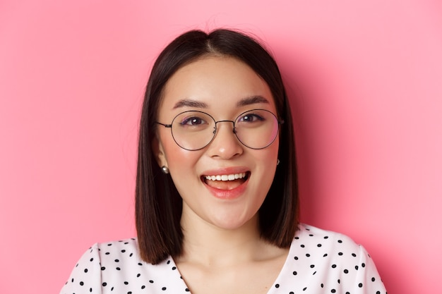Concetto di bellezza e stile di vita. primo piano del modello femminile asiatico carino che indossa occhiali alla moda, sorridendo felice alla telecamera, in piedi su sfondo rosa.