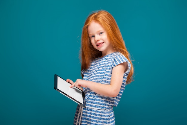 Beauty little girl in tee shirt with long hair, with tablet in hands