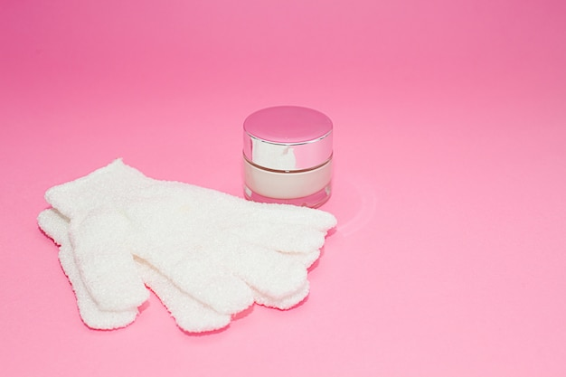 Beauty luxury cosmetic cream container and bath massage gloves on pink
