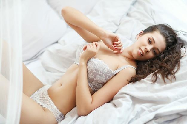 Красавица, лежа на кровати
