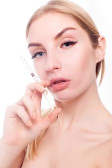 아름다움, 메이크업 및 사람들 개념 - 매력적인 젊은 여성은 흰색 배경 위에 격리된 화장품 주사를 받습니다. 의사가 얼굴에 주사를 맞고 있습니다. 뷰티 트리트먼트.