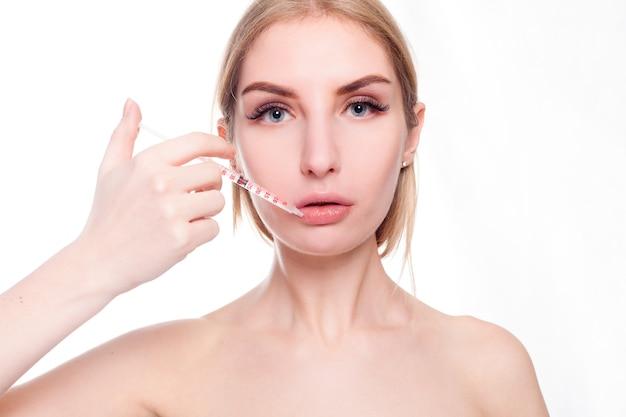 아름다움, 메이크업 및 사람들이 개념-매력적인 젊은 여자는 흰색 배경 위에 절연 화장품 주입을 가져옵니다. 의사는 얼굴에 주사를 손. 뷰티 트리트먼트.