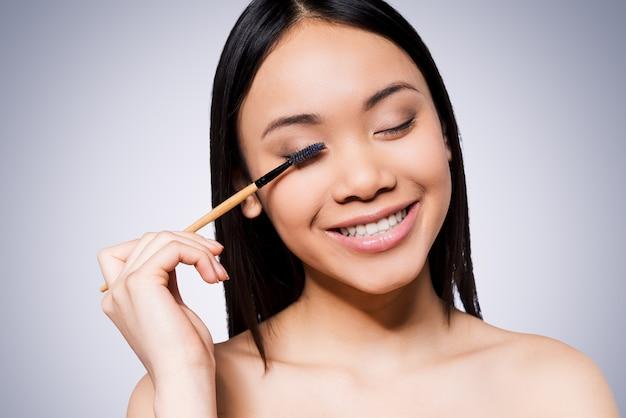 뷰티 메이크업입니다. 회색 배경에 서서 메이크업 브러시를 들고 웃고 있는 아름다운 젊고 셔츠를 입지 않은 아시아 여성