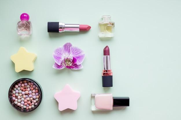 Красота. макияж кисти, лак для ногтей, флакон духов, все на пастельной стене, копией пространства. минималистская косметика настенные и цветки орхидеи. концепция красоты блогов.