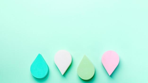 뷰티, 메이크업 스펀지 또는 뷰티 블렌더는 파스텔 색상의 아쿠아 멘테 색상 배경, 복사 공간, 위쪽 전망을 제공합니다. 미용 치료, 자기 관리 배경 오버 헤드