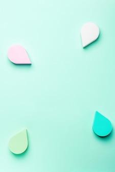 아름다움, 파스텔 색상 배경에 파스텔 색상의 스펀지 또는 미용 블렌더, 복사 공간, 위쪽 전망을 만듭니다. 트렌디한 색상의 아름다움 배경