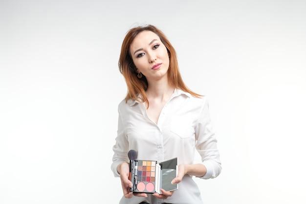 美容メイクアップアーティスト。白い壁にアイシャドウパレットブラシを保持してかなり笑顔の韓国の美しい若い女性を閉じます。