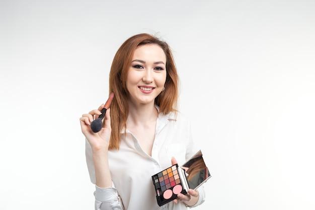 美容メイクアップアーティストがアイシャドウパレットを持ってかなり笑顔の韓国の美しい若い女性をクローズアップ