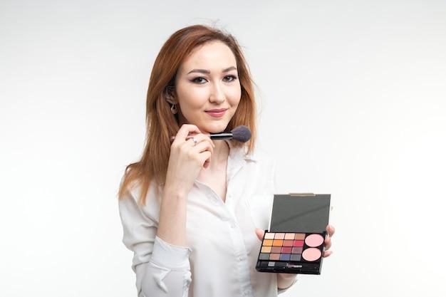 Визажист красоты. крупным планом корейская красивая молодая женщина довольно улыбается, держа тени для век