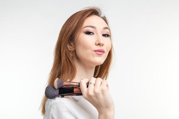 美容メイクアップアーティスト。白い壁に化粧ブラシを持ってかなり笑顔の韓国の美しい若い女性をクローズアップ