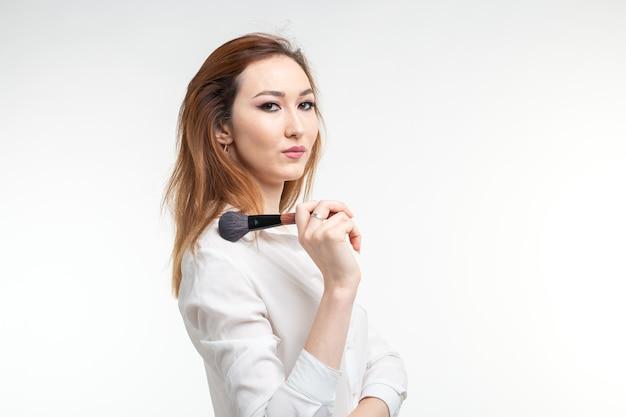 美容メイクアップアーティスト。メイクアップブラシを持ってかなり笑顔の韓国の美しい若い女性をクローズアップ。