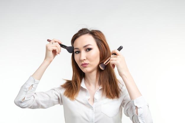 美容メイクアップアーティストは、化粧ブラシを持ってかなり笑顔の韓国の美しい若い女性をクローズアップ