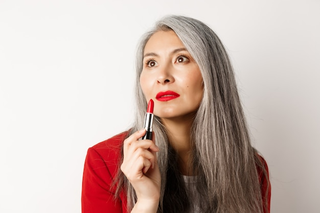 Beauty and makeup concept. sensual mature asian female with grey hair, looking aside and showing red lipstick, standing over white background.