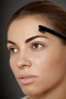 Beauty makeup. eyebrows care and  makeup. portrait of beautiful woman model shaping brown eyebrows.