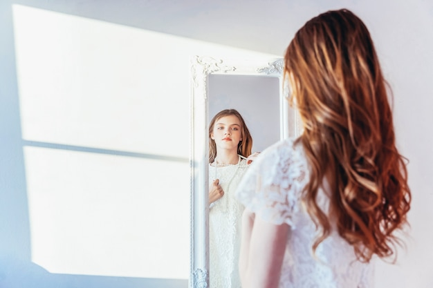 뷰티 메이크업 아침 루틴은 자신의 개념을 사랑합니다. 거울에 반사를 보고 어린 십 대 소녀입니다. 흰 벽에 밝은 빛의 방에서 포즈를 취하는 흰 드레스를 입은 젊은 긍정적인 여성.