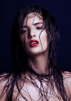 Beauty makeup wet hair fashion model with red lips on black wall