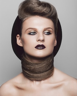 Beauty makeup with glamour hairstyle with hat on grey background