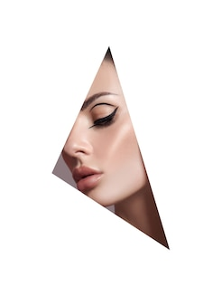 Beauty makeup women, eye brows eyelashes and lips in a triangular hole paper white background. professional beauty makeup, place for text, copy space Premium Photo